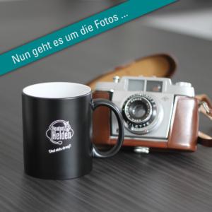 Kaffeebecher der HeadsetHelden und Fotokamera für den Fotowettbewerb